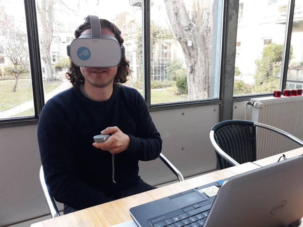 Ein junger Mann hat eine Virtual Reality-Brille auf und hält einen Controller in der Hand.