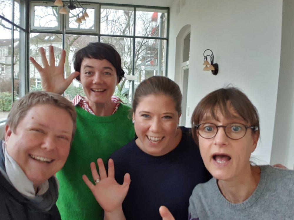Vier Mitarbeiterinnen des Career Centers lächeln und winken in die Kamera.