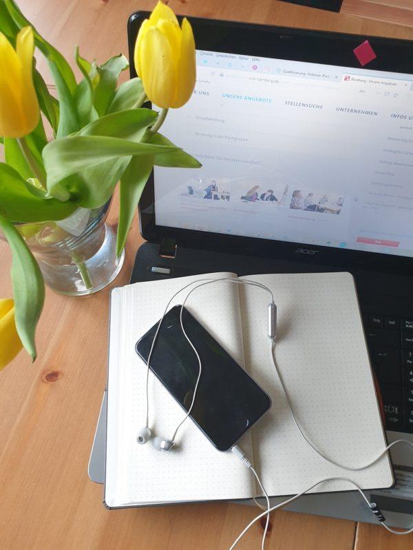 Auf der Tatstatur eines aufgeklappten Laptops liegt ein aufgeklapptes Notizbuch und ein Smartphone mit angeschlossenem Kopfhörer. Daneben steht eine Blumenvase mit gelben Tulpen.