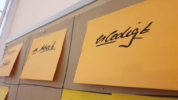 """Mit großen Klebezetteln ist ein Kanban-Board auf einer Pinnwand dargestellt, zu lesen sind die Abschnitte """"in Arbeit"""" und """"erledigt""""."""